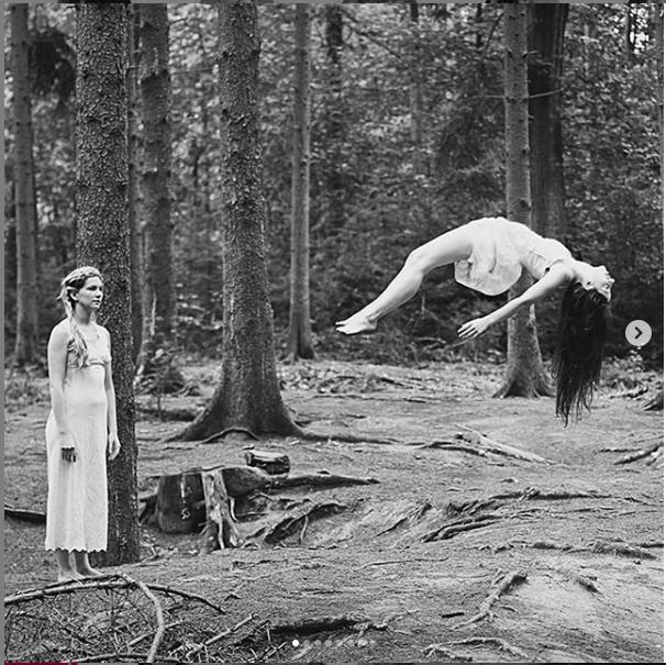 Un bosque y dos mujeres, una mira como la otra esta acostada de espalda flotando en el aire